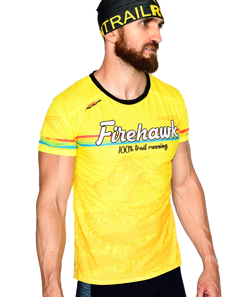 PERSPECTIVA DERECHA FRONTAL CAMISETA TRAIL RUNNING MODELO 100%TRAIL EN COLOR AMARILLO Y ESTAMPADO MONTAÑAS.