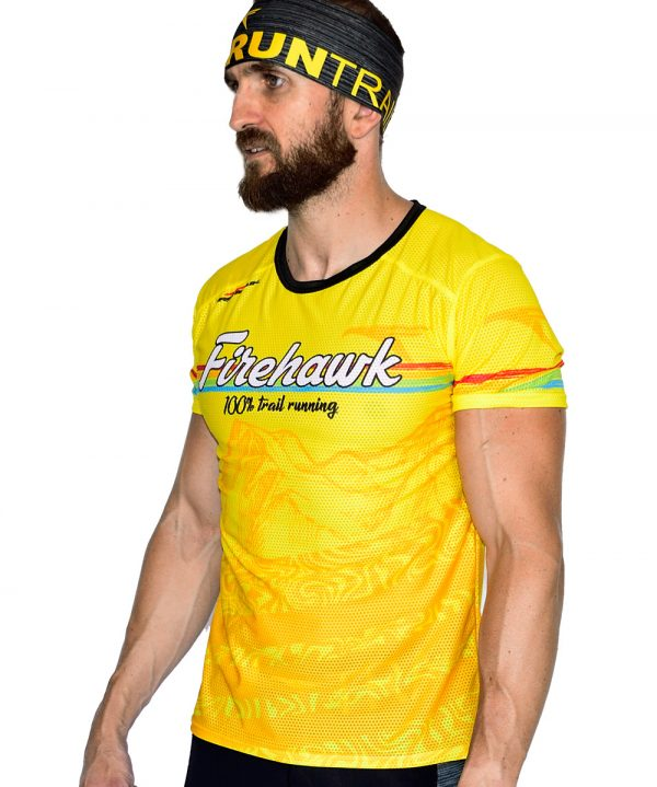 PERSPECTIVA IZQUIERDA FRONTAL CAMISETA TRAIL RUNNING MODELO 100%TRAIL EN COLOR AMARILLO Y ESTAMPADO MONTAÑAS.